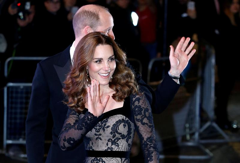 The royals are pictured waving to the crowds as they walked into the theater. (Photo: Henry Nicholls/Reuters)