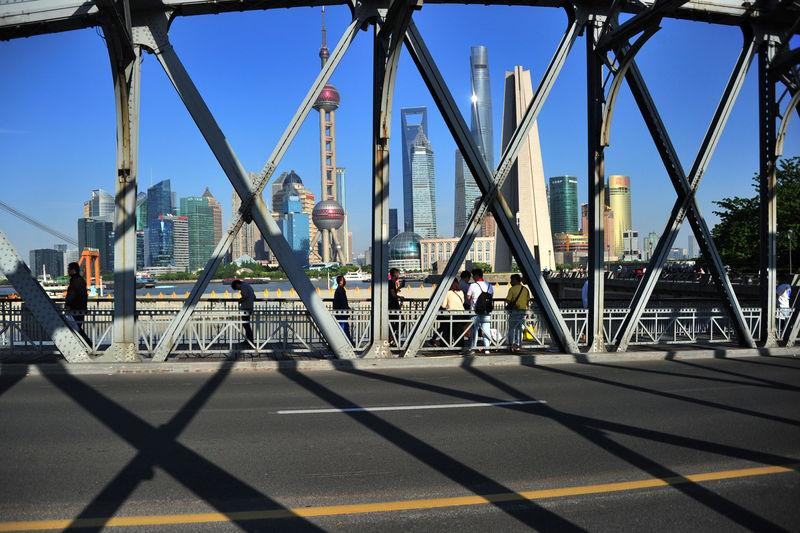 People walk on a bridge near the financial district of Pudong in Shanghai