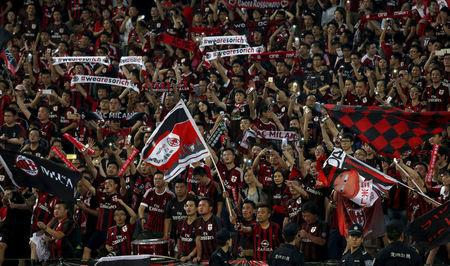 FILE PHOTO: Chinese fans of AC Milan wave with their mobile phones during the end of the International Champions Cup friendly match between AC Milan and Inter Milan in Shenzhen