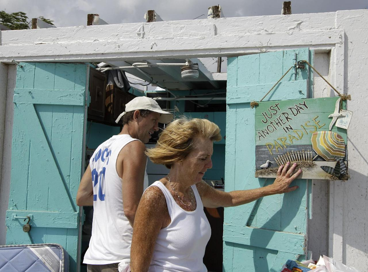 Bill Ryan watches as his wife Janet hangs up a picture in front of their roofless cabana at the Breezy Point Surf Club in the Queens section of New York, Saturday, Sept. 8, 2012, after severe weather passed the area. A tornado swept out of the sea and hit the beachfront neighborhood in New York City, hurling debris in the air, knocking out power and startling residents who once thought of twisters as a Midwestern phenomenon. Firefighters were still assessing the damage, but no serious injuries were reported and the area affected by the storm appeared small. (AP Photo/Kathy Willens)
