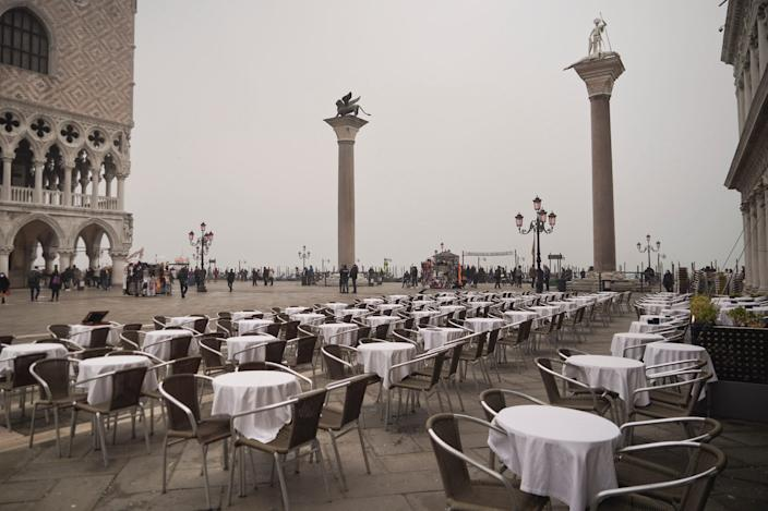 Empty tables sit in St. Mark's square in Venice, Italy, Tuesday, Feb. 25, 2020.