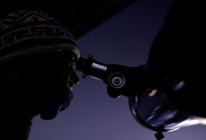 FILE PHOTO: Man observes the closest visible conjunction of Jupiter and Saturn, through a telescope in Kathmandu