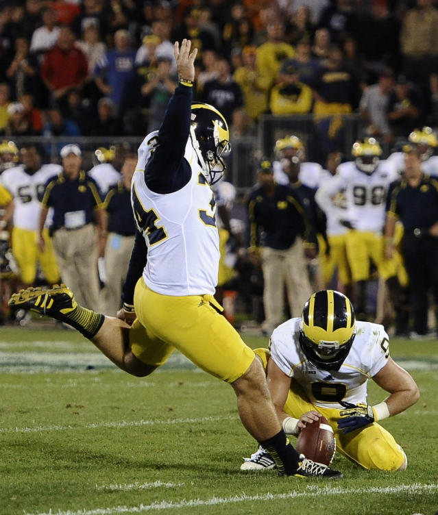 Michigan's Brendan Gibbons (34) kicks the go-ahead field goal as Drew Dileo holds during the second half of an NCAA college football game against Connecticut at Rentschler Field, Saturday, Sept. 21, 2013 in East Hartford, Conn. Michigan won 24-21. (AP Photo/Jessica Hill)
