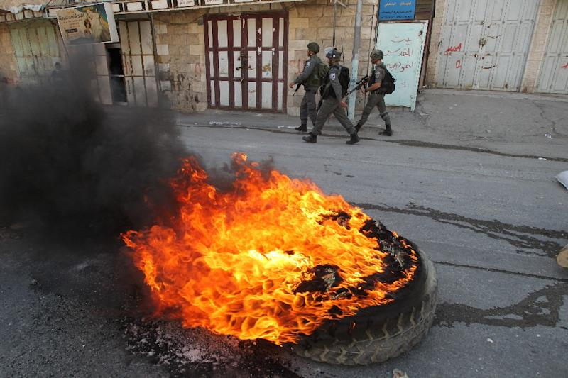 Israeli security forces walk past burning tires during clashes with Palestinian protesters in H2 (AFP Photo/Hazem Bader)