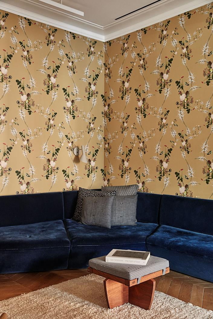 """<div class=""""caption""""> A Levenbetts sectional, George Nakashima stool, and Superflower's peony large wallpaper in the den. </div>"""