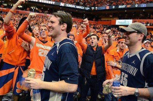 Syracuse fans heckle Georgetown fans Kris Henman, left, and Tom Cassels as they make their way to their seats before an NCAA college basketball game in Syracuse, N.Y., Saturday, Feb. 23, 2013. (AP Photo/Kevin Rivoli)