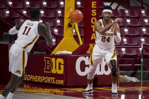 FILE - In this Nov. 25, 2020, file photo, Minnesota forward Eric Curry (24) passes the ball during the first half of the team's NCAA college basketball game against Green Bay in Minneapolis. Curry texted his mom last week. He needed a headshot of her and his sister, in an effort by the fifth-year senior forward to give his closest family members the chance, virtually, to be present for Minnesota's upcoming games. When the Gophers host Iowa at an empty Williams Arena on Christmas night, the good tidings of great joy will have to come from those cardboard faces of parents, siblings and friends strategically placed in prime seats nearest the court.(AP Photo/Bruce Kluckhohn, File)