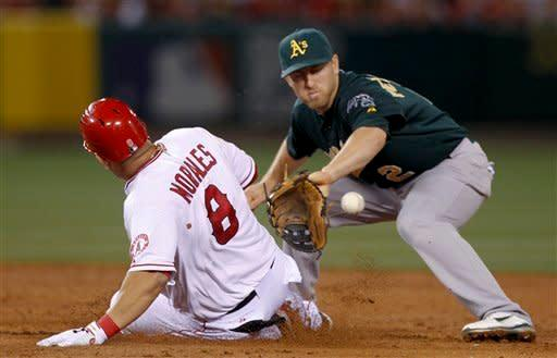 Los Angeles Angels' Kendrys Morales, left, slides before being tagged out at second trying to extend a single into a double, by Oakland Athletics shortstop Cliff Pennington during the third inning of a baseball game in Anaheim, Calif., Monday, April 16, 2012. (AP Photo/Chris Carlson)