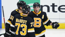Boston Bruins' Brad Marchand, right, is congratulated by Charlie McAvoy (73) and Jeremy Lauzon (55) after his short-handed goal against the Pittsburgh Penguins during the first period of an NHL hockey game, Tuesday, Jan. 26, 2021, in Boston. (AP Photo/Charles Krupa)
