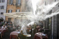 FILE - In this Friday, July 31, 2020 file photo, a fan sprays water mist as customers sit outside a cafe in downtown Rome during a heat wave with temperatures over 34 Celsius (104 Fahrenheit). (AP Photo/Riccardo De Luca)
