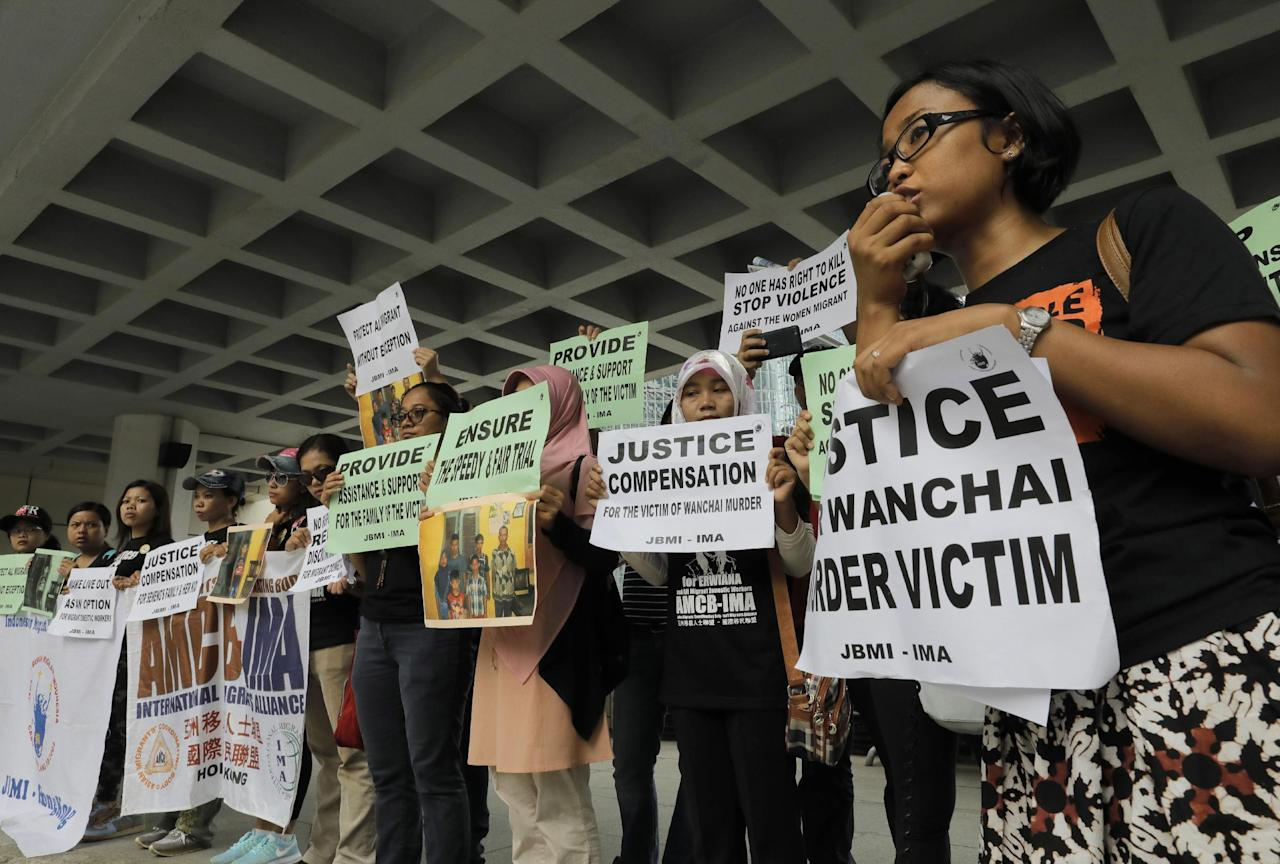 A migrant workers alliance group holds placards to protest the killings of two Indonesian women in 2014 outside the High Court in Hong Kong, Monday, Oct. 24, 2016. British banker Rurik Jutting accused of the grisly 2014 killings pleaded not guilty when he went on trial Monday, in a case expected to highlight the Asian financial hub's inequality and privileged lifestyle of its wealthy expat elite. (AP Photo/Vincent Yu)