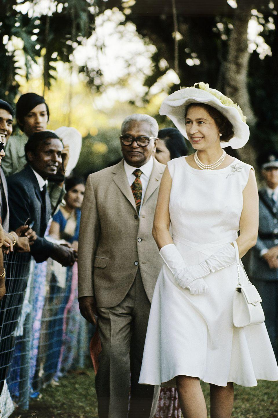 <p>In a stunning all white outfit during a walkabout in the Mauritius as part of her Silver wedding anniversary celebrations. </p>