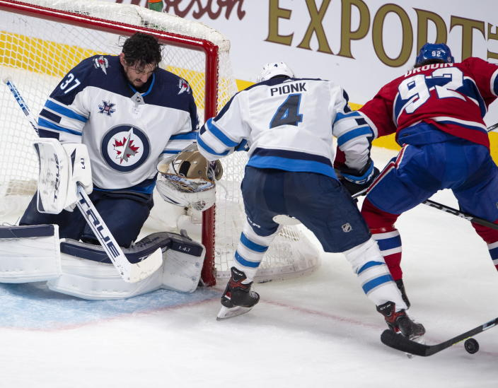 Winnipeg Jets goaltender Connor Hellebuyck (37) catches his mask after making a save as Montreal Canadiens' Jonathan Drouin (92) and Jets' Neal Pionk (4) battle for the rebound during the second period of an NHL hockey game, Thursday, April 8, 2021 in Montreal. (Ryan Remiorz/The Canadian Press via AP)