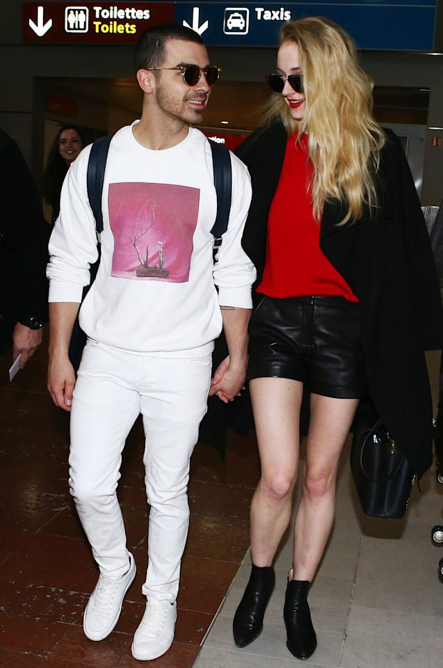 """<p>The adorable couple were spotted at the airport in Paris, touching down just in time for the last few days of Paris Fashion Week. Jonas rocked an all-white look, while Turner looked chic in a black miniskirt, red top, and long black Mackage coat ($590; <a rel=""""nofollow"""" href=""""http://www.anrdoezrs.net/links/7799179/type/dlg/sid/ISHASTJJAIRPORTMARCH2017/http://www.mackage.com/us/en/loni-long-double-face-wool-coat-in-black-for-women"""">mackage.com</a>).</p>"""
