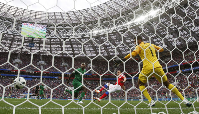 Russia's Artyom Dzyuba, center, scores his side's third goal past Saudi Arabia goalkeeper Abdullah Almuaiouf during the group A match between Russia and Saudi Arabia which opens the 2018 soccer World Cup at the Luzhniki stadium in Moscow, Russia, Thursday, June 14, 2018. (AP Photo/Antonnio Calanni)