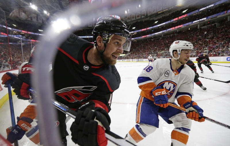 Carolina Hurricanes' Calvin de Haan, left, and New York Islanders' Anthony Beauvillier (18) chase the puck during the second period of Game 4 of an NHL hockey second-round playoff series in Raleigh, N.C., Friday, May 3, 2019. (AP Photo/Gerry Broome)
