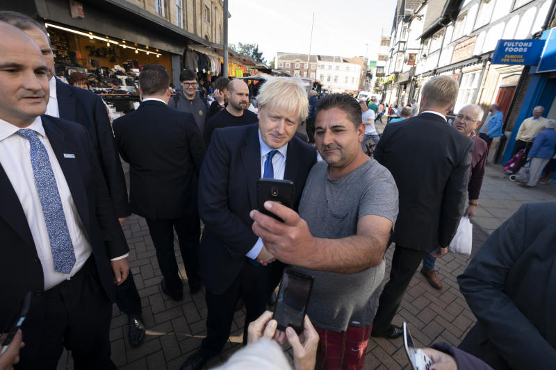 Britain's Prime Minister Boris Johnson poses for a selfie with a member of the public during a visit to Doncaster Market, in Doncaster, Northern England, Friday Sept. 13, 2019. Johnson will meet with European Commission president Jean-Claude Juncker for Brexit talks Monday in Luxembourg. The Brexit negotiations have produced few signs of progress as the Oct. 31 deadline for Britain's departure from the European Union bloc nears. ( AP Photo/Jon Super)