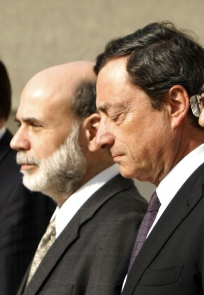 FILE- In this Friday, April 11, 2008, file photo, Ben Bernanke, left, and Mario Draghi, right, pose for a group photo at the Treasury Department's Cash Room in Washington. Draghi, the European Central Bank president, is overtaking the Federal Reserve chairman as the central banker with the most influence on the global economy and markets. Faced with a growing recession and a possible breakup of the 17-country euro alliance, Draghi has bigger problems than Bernanke, who's overseeing an economy in recovery. As head of the ECB, which meets Thursday, Sept. 6, 2012, Draghi also has more ammunition left than Bernanke does. (AP Photo/Gerald Herbert, File)