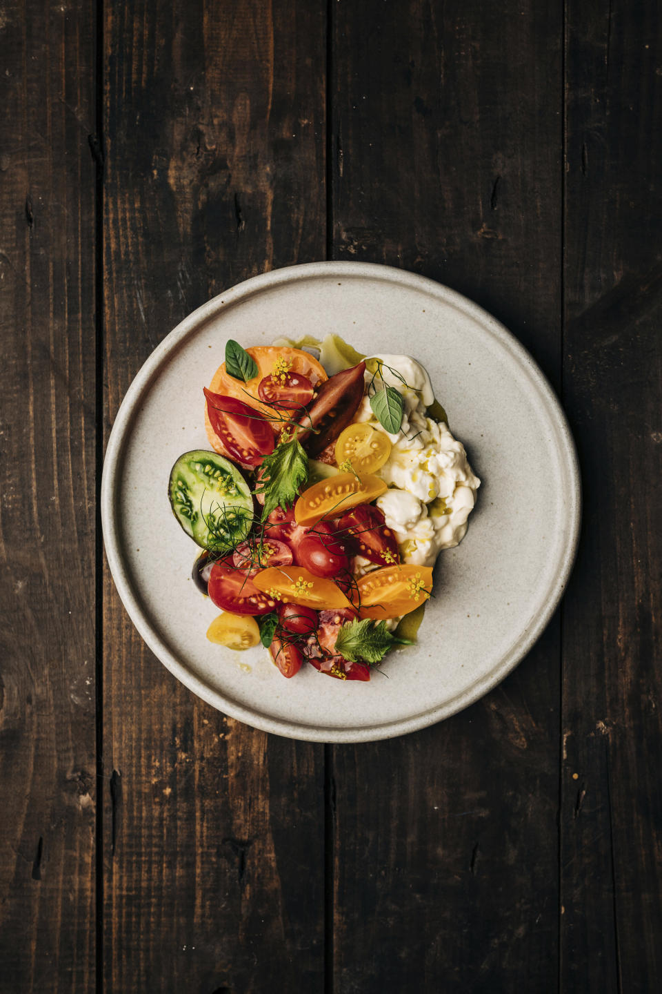 """This image released by Hardie Grant Books shows a recipe consisting of tomatoes and peaches with honey vinegar and burrata curds from the cookbook """"How Wild Things Are: Cooking, Fishing and Hunting at the Bottom of the World,"""" by Analiese Gregory. (Adam Gibson/Hardie Grant Books via AP)"""