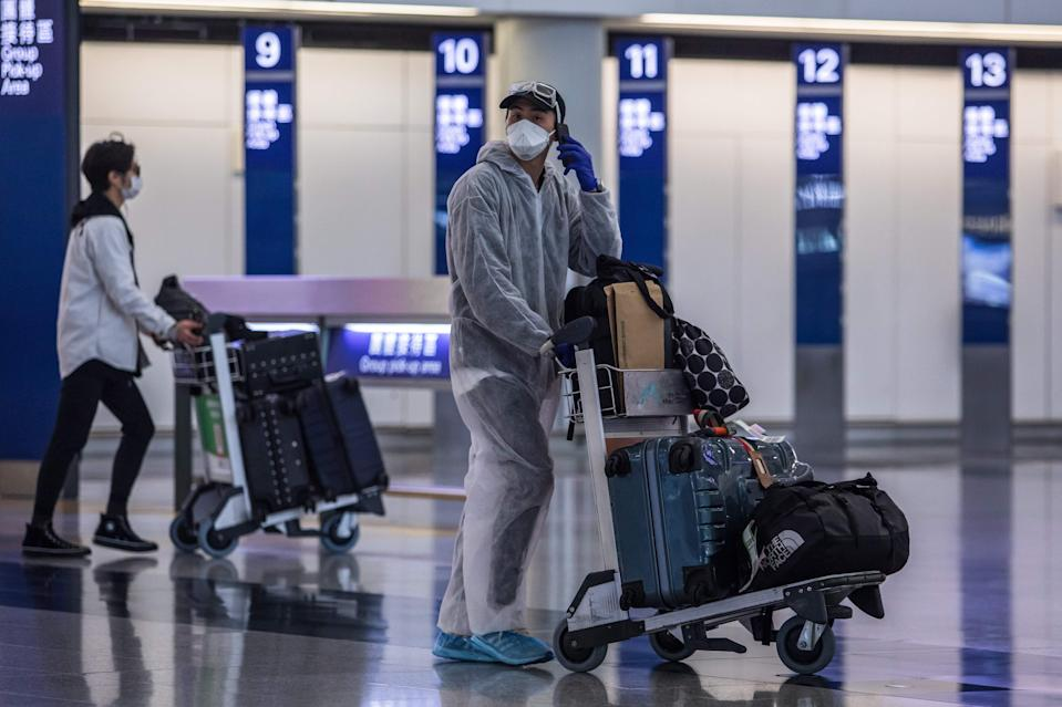 File: A passenger wearing a face mask and protective suit at the Hong Kong International Airport on 4 April, 2020 (AFP via Getty Images)