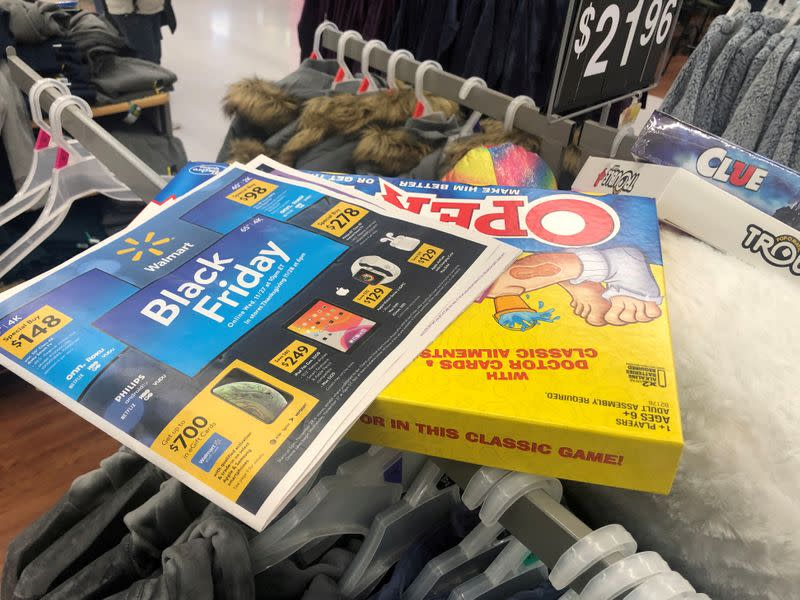 FILE PHOTO: Black Friday ads lay on top of clothes during a sales event on Thanksgiving day at Walmart in Westbury, New York