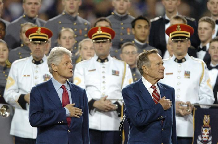Former US presidents George H.W. Bush (R) and Bill Clinton listen to the national anthem sung by the combined choirs of the U.S. Military Academy the U.S. Naval Academy, the U.S. Air Force Academy, and the U.S. Coast Guard Academy, and the U.S. Army Herald Trumpets before the start of Super Bowl XXXIX between the Philadelphia Eagles and the New England Patriots on Feb. 6, 2005 at Alltel Stadium in Jacksonville, Florida.