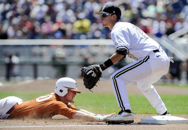 Texas' Zane Gurwitz, left, reaches third base on a triple against Vanderbilt third baseman Tyler Campbell (2) in the inning of an NCAA baseball College World Series game in Omaha, Neb., Friday, June 20, 2014. (AP Photo/Eric Francis)