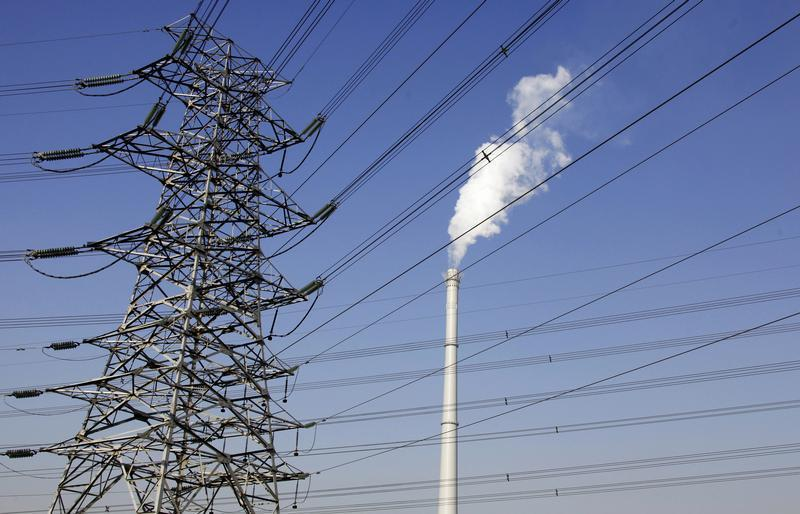 A chimney billows smoke behind electricity wires in central Beijing