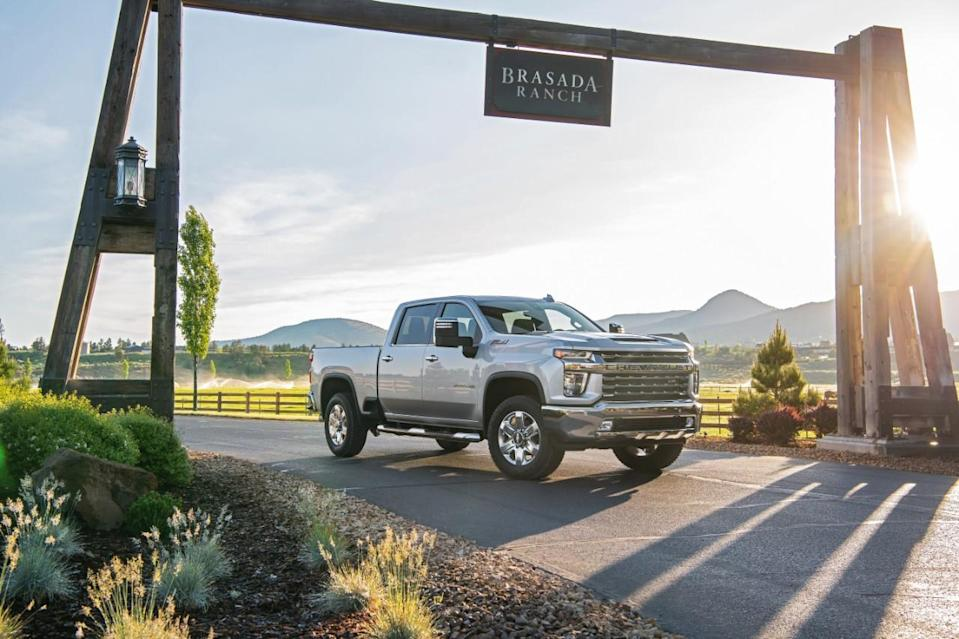 """Silverado truck parked in front of a sunset, under a sign that reads """"Brasada Ranch."""""""