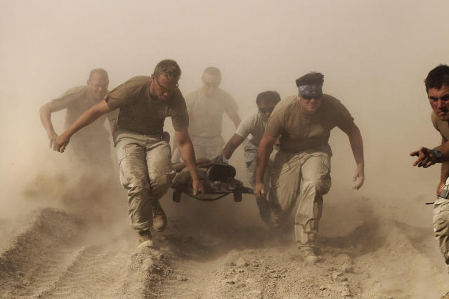 <p>Members of the U.S. Navy carry a comrade wounded by an explosion to a medevac helicopter in Kandahar province in southern Afghanistan, Oct. 2, 2010. (Photo: Finbarr O'Reilly/Reuters) </p>
