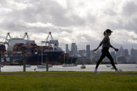A woman takes a walk in a park during lockdown due to the continuing spread of the coronavirus in Melbourne, Thursday, Aug. 6, 2020. Victoria state, Australia's coronavirus hot spot, announced on Monday that businesses will be closed and scaled down in a bid to curb the spread of the virus. (AP Photo/Andy Brownbill)