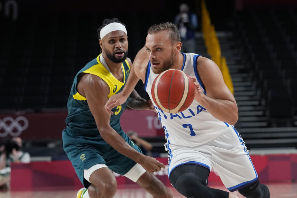 Italy's Stefano Tonut (7) drives around Australia's Patty Mills (5) during a men's basketball preliminary round game at the 2020 Summer Olympics, Wednesday, July 28, 2021, in Saitama, Japan. (AP Photo/Eric Gay)