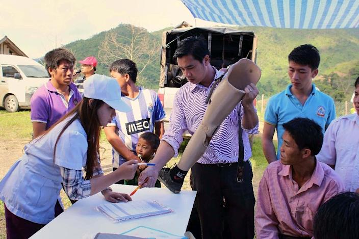Workers from COPE (Cooperative Orthotic and Prosthetic Enterprise) hold up a prosthetic leg at a mobile clinic in Xieng Khoang, Laos on June 2, 2016 (AFP Photo/Coraline Molinie)