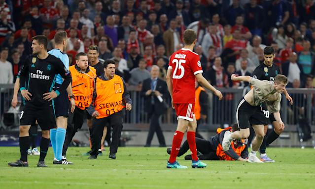 Soccer Football - Champions League Semi Final First Leg - Bayern Munich vs Real Madrid - Allianz Arena, Munich, Germany - April 25, 2018 Stewards attempt to tackle a pitch invader after the match as Real Madrid's Cristiano Ronaldo looks on REUTERS/Kai Pfaffenbach