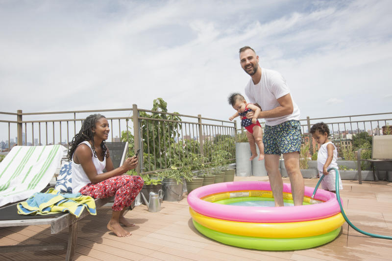 Parents playing with children in inflatable swimming pool