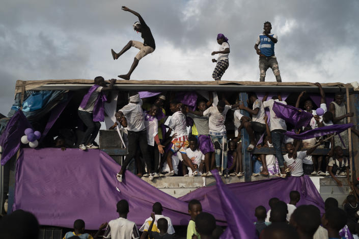 Supporters of the presidential candidate Kouadio Konan Bertin, dance over a sound truck during the final campaign rally in Abidjan, Ivory Coast, Thursday, Oct. 29, 2020. Bertin, known as KKB, has presented his candidacy as an independent candidate for the upcoming Oct. 31 election, and said he would not join the boycott proposed by two main opponents of Ivory Coast President Alassane Ouattara. (AP Photo/Leo Correa)