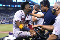Atlanta Braves right fielder Ronald Acuna Jr., left, leaves the field on a medical cart after trying to make a catch on an inside-the-park home run hit by Miami Marlins' Jazz Chisholm Jr. during the fifth inning of a baseball game Saturday, July 10, 2021, in Miami. (AP Photo/Lynne Sladky)