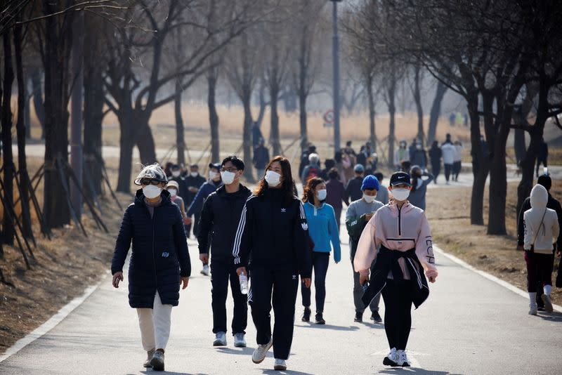 People wearing masks take a walk amid the coronavirus disease (COVID-19) pandemic at a Hanriver Park in Seoul