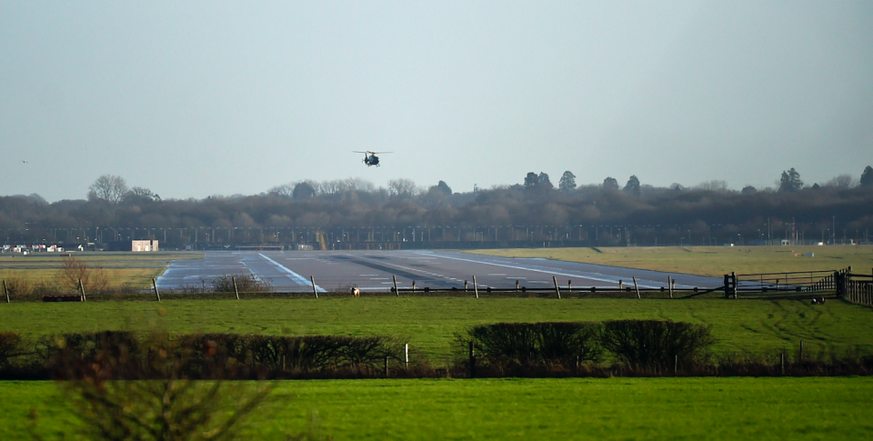 <em>The helicopter flies over the runway as the search continues for the drones and their operators (PA)</em>
