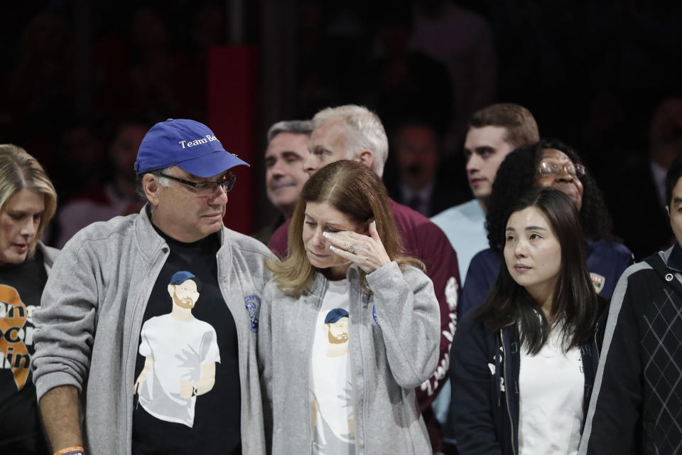 FILE - In this Feb. 17, 2019, file photo, Linda Beigel Schulman, right, wipes a tear from her eye as she stands with her husband, Michael Schulman, in honor of the survivors of the mass shooting at Marjory Stoneman Douglas High School in Florida. Michael Schulman, the father of shooting victim Scott Beigel, wrote a newspaper opinion piece in which he said it would be better for everyone if the defendant, Nikolas Cruz, could plead guilty and be locked away for life. (AP Photo/Brynn Anderson, File)
