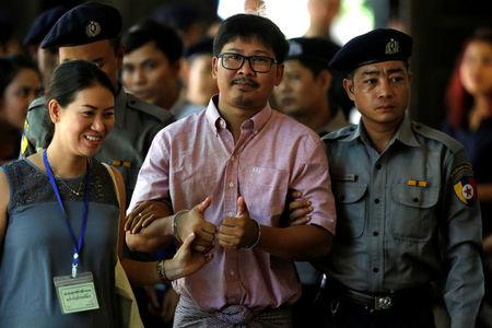 Detained Reuters journalist Wa Lone is escorted by police before a court hearing in Yangon, Myanmar May 16, 2018. REUTERS/Ann Wang