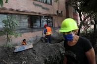 Resident Angelica Serna wears a protective helmet as she walks past workers checking a wall of an apartment building damaged by an earthquake that struck southern Mexico on Tuesday, in Mexico City