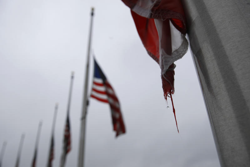 FILE - In this May 22, 2020, file photo, a raindrop falls from an American flag at half-staff at the Washington Monument, in Washington. President Donald Trump ordered American flags to be flown at half-staff for a three day period in remembrance of Americans who have lost their lives due to the coronavirus outbreak. (AP Photo/Patrick Semansky, File)