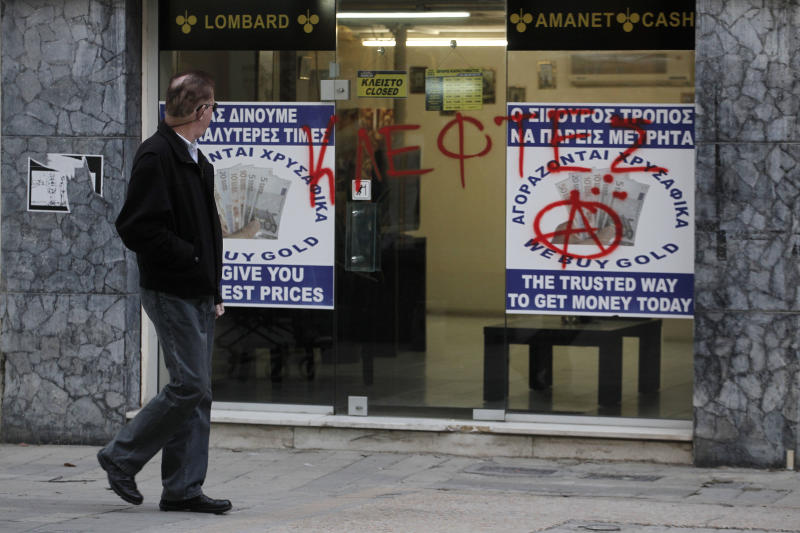 """A man passes a sprayed entrance of a store that buys gold which reads in Greek """" thieves"""" in capital Nicosia, Cyprus, Monday, March 25, 2013.  Cyprus secured what its politicians described as a """"painful"""" solution to avert imminent bankruptcy, agreeing early Monday to slash its oversize banking sector and make large account holders take losses to help pay to secure a last-minute euro10 billion (US$13 billion) bailout. (AP Photo/Petros Giannakouris)"""