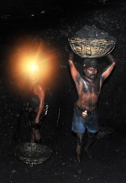 A file photo shows Indian coal miners carrying coal inside a mine near Hyderabad in 2010. India's top court cancelled more than 200 government permits for coal mines (AFP Photo/Noah Seelam)