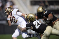 Minnesota quarterback Tanner Morgan, left, is dragged down by Colorado linebacker Carson Wells and defensive lineman Jalen Sami in the second half of an NCAA college football game Saturday, Sept. 18, 2021, in Boulder, Colo. Minnesota won 30-0. (AP Photo/David Zalubowski)