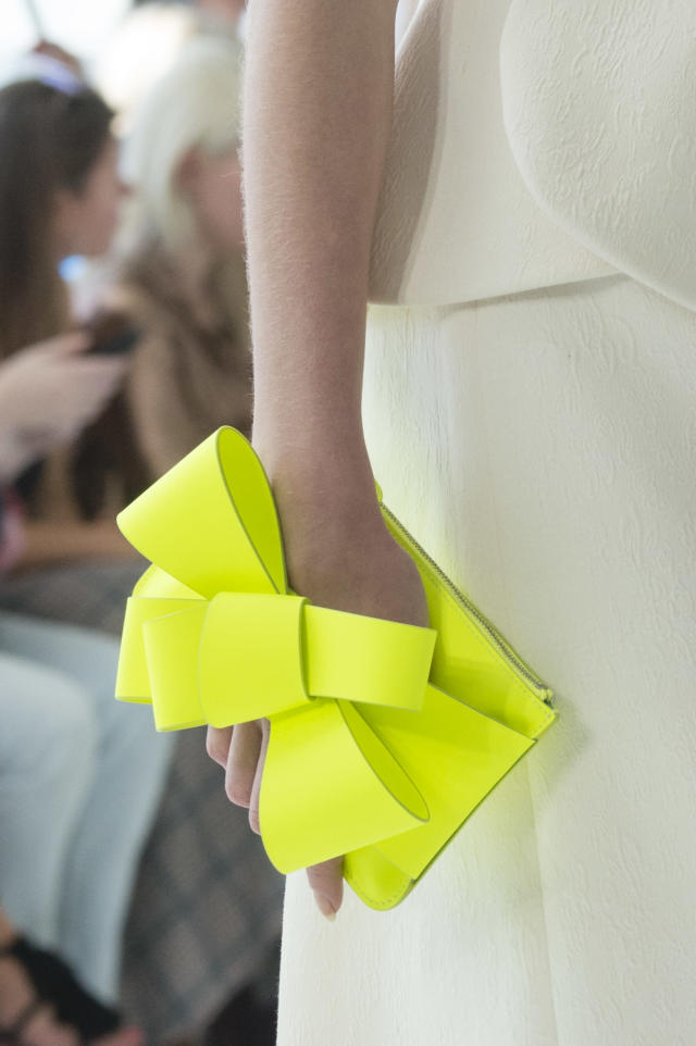 <p><i>Bright-yellow-green bow hand clutch from the SS18 Delpozo collection. (Photo: ImaxTree) </i></p>