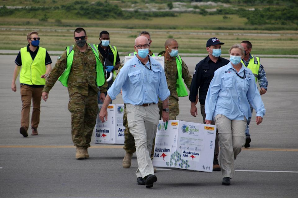 Australian officials carry boxes containing vaccines on PNG airstrip.