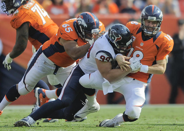 FILE - In this Sept. 23, 2012, file photo, Denver Broncos quarterback Peyton Manning (18) is sacked by Houston Texans defensive end J.J. Watt (99) as guard Manny Ramirez (65) tries to block Watt during an NFL football game in Denver. Watt's sacks have gone down from 20 last season to 9 this year, but the Broncos contend this is another case where the numbers don't tell the whole story. The two teams meet again on Sunday, Dec. 22. (AP Photo/Jack Dempsey, File)