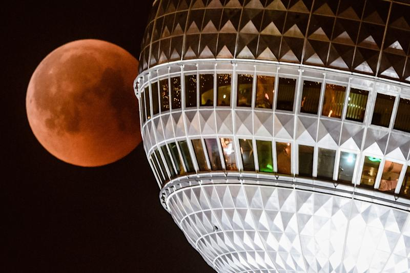 Berlin (Germany), 27/07/2018.- The red colored moon can be seen next to Berlin TV Tower in Berlin, 27 July 2018. The lunar eclipse on the night of 27 July 2018 will be the longest total lunar eclipse of the 21st century with the event spanning for over four hours, and the total eclipse phase lasting for 103 minutes. (Alemania) EFE/EPA/CLEMENS BILAN